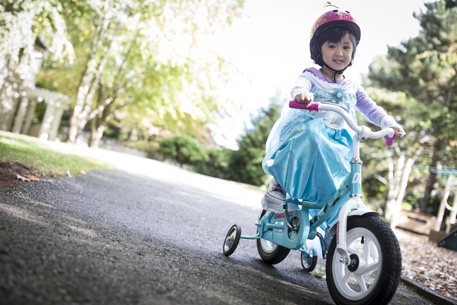 girl rides bike in halloween costume