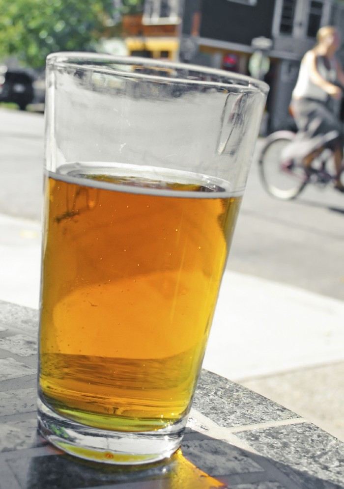 Glass of beer on sidewalk table