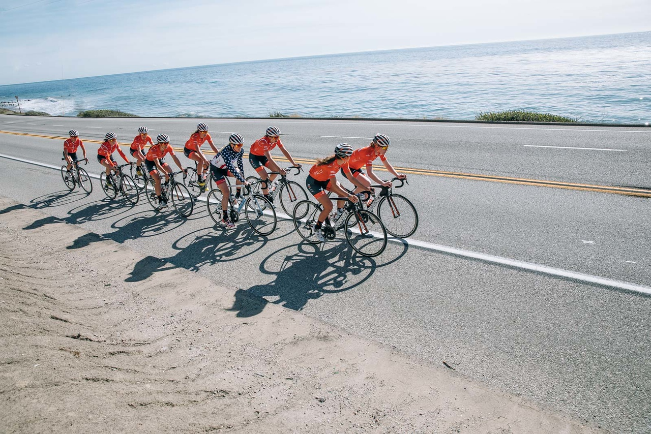 Rally Cycling women's team riding in a group by the ocean in California